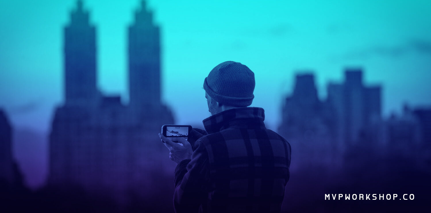 Man with a winter cap taking a photo with blurred city in the background