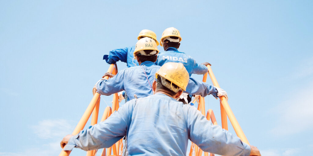 Workers with yellow helmets climbing a stairway to heaven