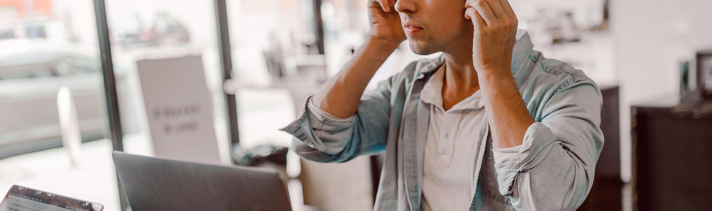 man listening on headphones carefully